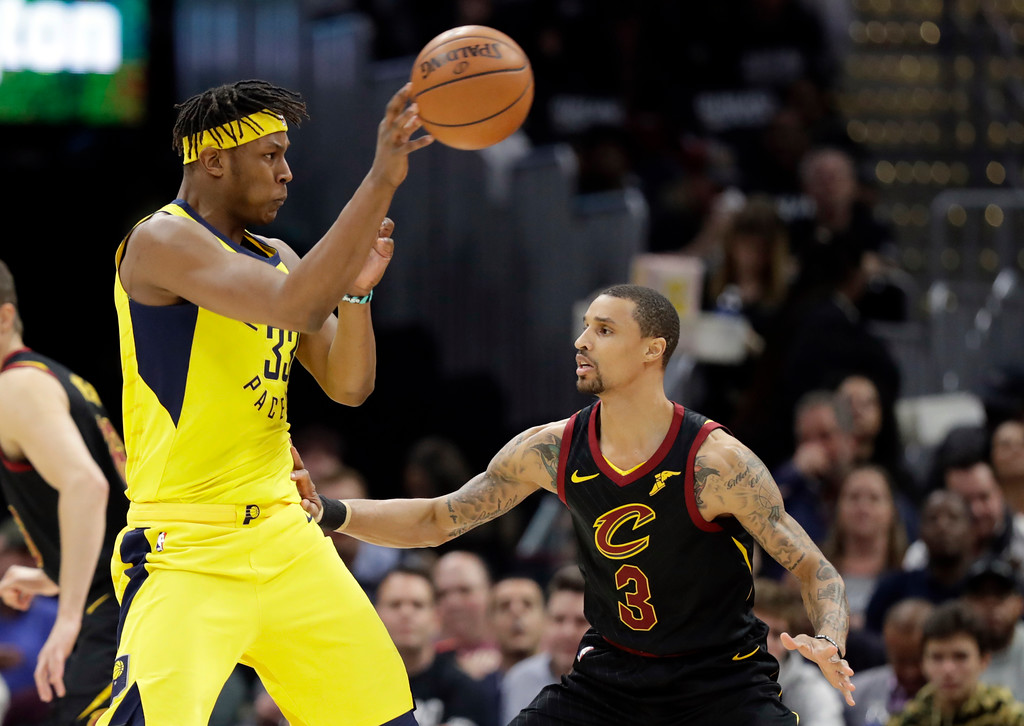 . Indiana Pacers\' Myles Turner (33) passes the ball over Cleveland Cavaliers\' George Hill (3) during the first half of Game 2 of an NBA basketball first-round playoff series Wednesday, April 18, 2018, in Cleveland. (AP Photo/Tony Dejak)