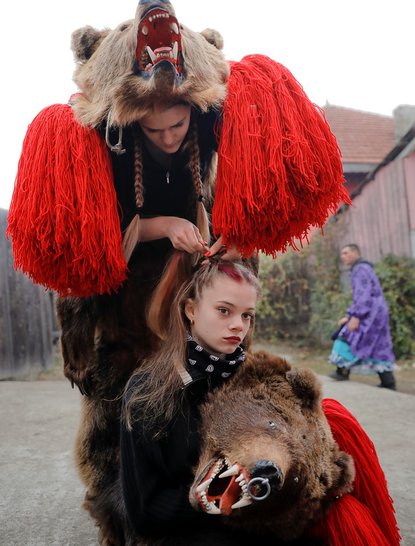 . In this Saturday, Dec. 30, 2017 picture, Roxana Stan, top, braids Raluca Atrejei\'s hair as they get ready for an annual bear parade in Asau, Romania. Hundreds of people descend on the sleepy northern Romanian city of Comanesti every year dressed head to toe like bears, in costumes made from real fur, with the heads attached. It\'s a tradition that originated in pre-Christian times, when dancers wearing colored costumes or animal furs went from house to house in villages, singing and dancing to ward off evil. (AP Photo/Vadim Ghirda)