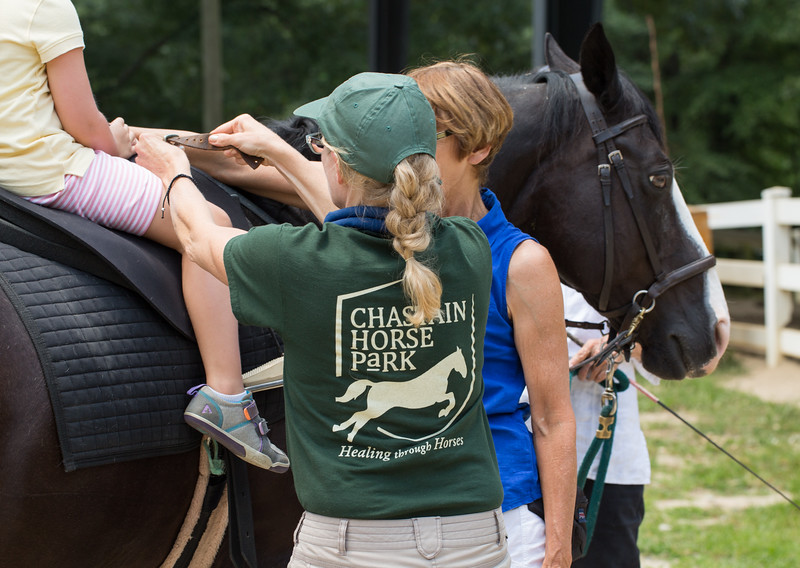 Sue Soha is a physical therapist at Chastain Horse Park and is helping 5-year-old Brooke Campbell get situated on her horse Gator before her therapy begins.  The center provides therapeutic programs for special needs campers and for those in need of physical and occupational therapies.  The program is comprised of professional therapist, equestrians and volunteers.    (Jenni Girtman / Atlanta Event Photography)