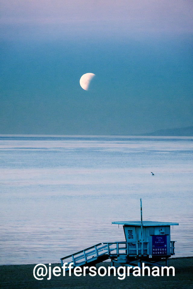 On the morning of the 2018 Super Moon, a Manhattan Beach lifeguard station, set against the morning moon
