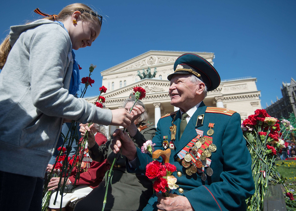 . A girl presents flowers to a World War II veteran during Victory Day celebrations in Moscow, on May 9, 2014. Russia and ex-Soviet republics marked today the 69 years since the Soviet victory over Nazi Germany in the World War II. AFP PHOTO / ANATOLY  TANIN/AFP/Getty Images