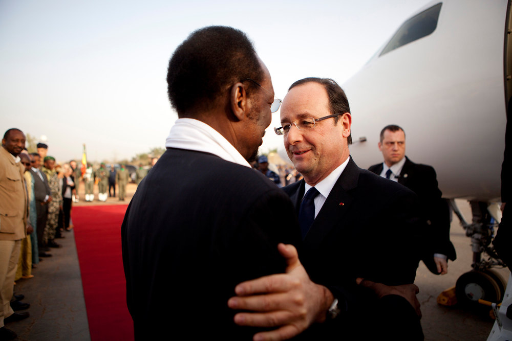 Description of . French President Francois Hollande, center right, is greeted by Mali\'s President Dioncounda Traore, as he arrives at the airport in Sevare, Mali, en route to Timbuktu, Saturday, Feb. 2, 2013. Hollande landed Saturday in the fabled Malian town of Timbuktu, making a triumphant stop six days after French forces parachuted in to liberate the desert city from the rule of al-Qaida-linked militants. (AP Photo/Malin Palm)