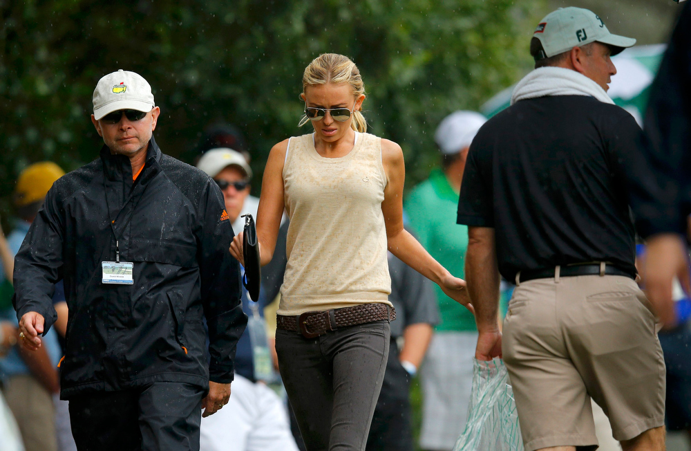 Description of . Golfer Dustin Johnson's girlfriend Paulina Gretzky (C) and agent David Winkle (L) follow him on the third hole during second round play in the 2013 Masters golf tournament at the Augusta National Golf Club in Augusta, Georgia, April 12, 2013.   REUTERS/Brian Snyder