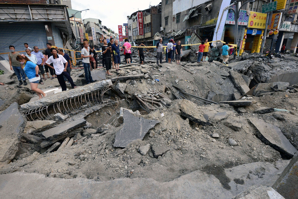 . Local residents look at the damage caused by gas explosions in the southern Taiwan city of Kaohsiung on August 1, 2014. A series of powerful gas blasts killed at least 25 people and injured up to 267 in the southern Taiwanese city of Kaohsiung, overturning cars and ripping up roads as terrified residents fled an inferno.     AFP PHOTO  / SAM YEH/AFP/Getty Images