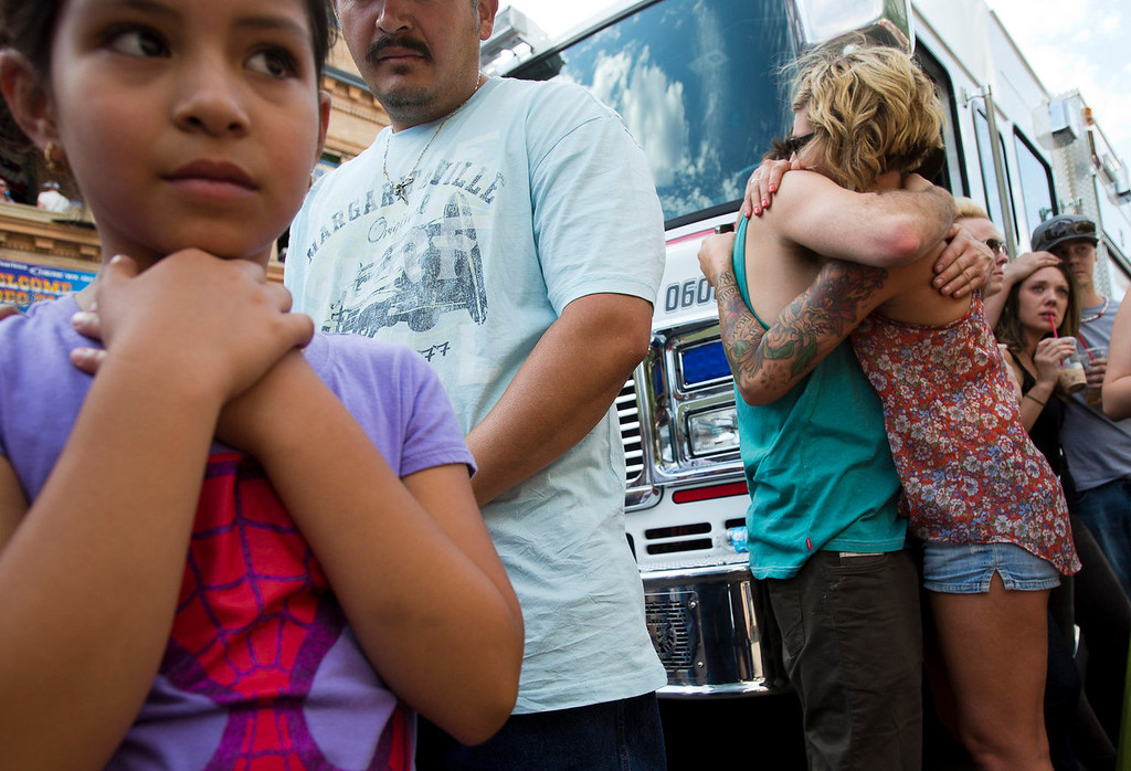 . Andrea Pendaloza, 7, from Prescott, watches a procession of hearses carrying 19 firefighters drove through downtown Prescott, Ariz., Sunday, July 7, 2013. Nineteen members of the Granite Mountain Hotshot crew died June 30 fighting the Yarnell Hills Fire, about 40 miles southwest of Prescott, Ariz. (AP Photo/The Arizona Republic, Michael Chow)