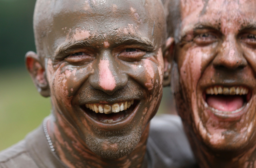 ". Participants of the ""Tough Mudder\"" endurance event series runs are seen with mud-covered faces after clearing the \""Mud Mile\"" obstacle in the Fursten Forest, a former British Army training ground near the north-western German city of Osnabrueck July 13, 2013. The hardcore but un-timed event over 16 km (10 miles) was designed by British Special Forces to test mental as well as physical strength. Some 4,000 competitors had to overcome obstacles of common human fears, such as fire, water, and heights.   REUTERS/Wolfgang Rattay"