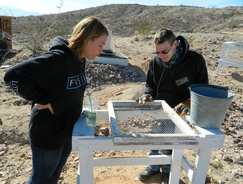 . Archaeologist and volunteer Michelle Nagy, left, helps a volunteer in a class at the Early Man Site near Yermo, CA, Jan. 4, 2014. The class teaches how to carefully clear an area in search for relicts from early man.  Once cleared, the sand and rocks are sent through a screen to make sure nothing important has been missed. (Photo by Joe Blackstock/Staff)