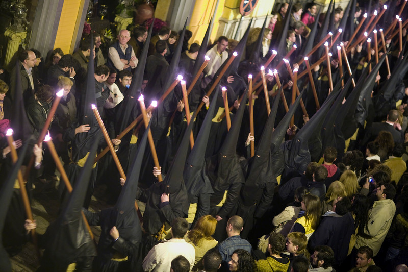 Hooded penitents bearing candles on Good Friday, Seville, Spain