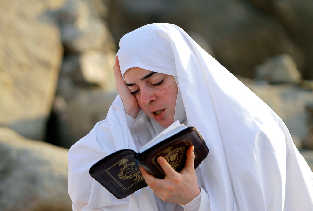 . A Muslim pilgrim reads verses from Islam\'s holy book the Quran on a rocky hill called the Mountain of Mercy, near the holy city of Mecca, Saudi Arabia, Monday, Oct. 14, 2013. The hajj, a central pillar of Islam and one that able-bodied Muslims must make once in their lives, is a four-day spiritual cleansing based on centuries of interpretation of the traditions of Prophet Muhammad. Women are tasked to look inward rather than on their appearances by giving up perfume, makeup and fitted outfits for long, loose clothing and a headscarf that covers the hair. (AP Photo/Amr Nabil)