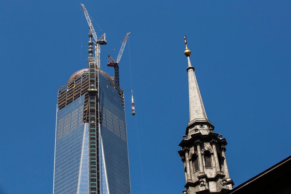 . The steeple of St. Paul\'s Chapel rises into the sky as the final piece of the building\'s spire is lifted to the top of One World Trade Center in New York, May 2, 2013. REUTERS/Lucas Jackson