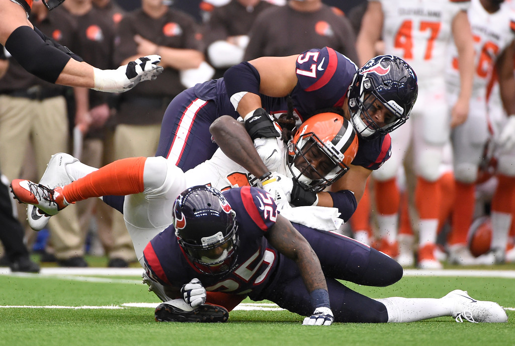 . Houston Texans linebacker Brennan Scarlett (57) and cornerback Kareem Jackson, bottom, stop Cleveland Browns running back Isaiah Crowell (34) from gaining yardage on a run in the first half of an NFL football game, Sunday, Oct. 15, 2017, in Houston. (AP Photo/Eric Christian Smith)