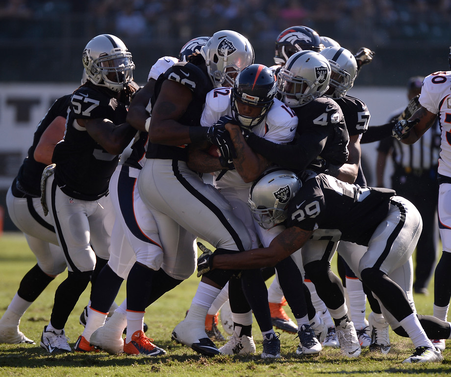 . OAKLAND, CA. - NOVEMBER 09: Denver Broncos Andre Caldwell (12) gets stopped by the Oakland Raiders special teams during a kickoff return during the first quarter November 9, 2014 at O.co Coliseum. (Photo By John Leyba/The Denver Post)