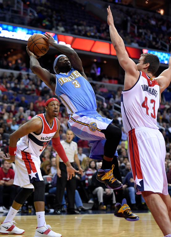 . Denver Nuggets guard Ty Lawson (3) prepares to throw the ball against Washington Wizards forward Kris Humphries (43) and Paul Pierce (34) during the first half of an NBA basketball game, Friday, Dec. 5, 2014, in Washington. (AP Photo/Nick Wass)