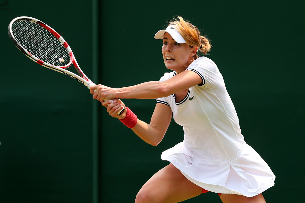 . Alize Cornet of France plays a backhand during her Ladies\' Singles second round match against  Su-Wei Hsieh of Taipei on day three of the Wimbledon Lawn Tennis Championships at the All England Lawn Tennis and Croquet Club on June 26, 2013 in London, England.  (Photo by Julian Finney/Getty Images)