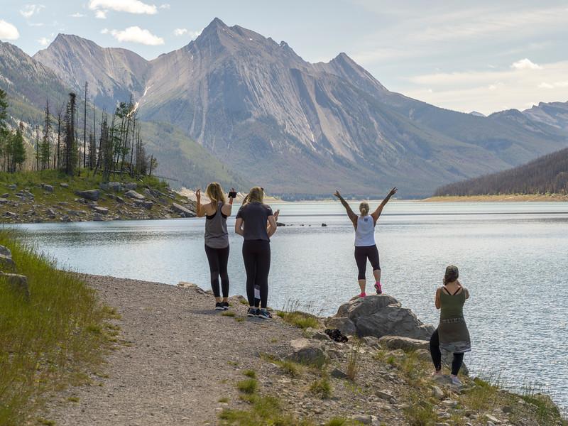Enthusiastic tourists at lakeside, Medicine Lake, Maligne Lake Road, Jasper National Park, Jasper, Alberta, Canada