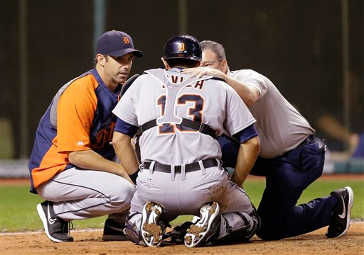 . Detroit Tigers manager Brad Ausmus, left, and a trainer talk with catcher Alex Avila after Avila was hit with the ball in the sixth inning of a baseball game, Tuesday, Sept. 2, 2014, in Cleveland. Avila left the game. (AP Photo/Tony Dejak)