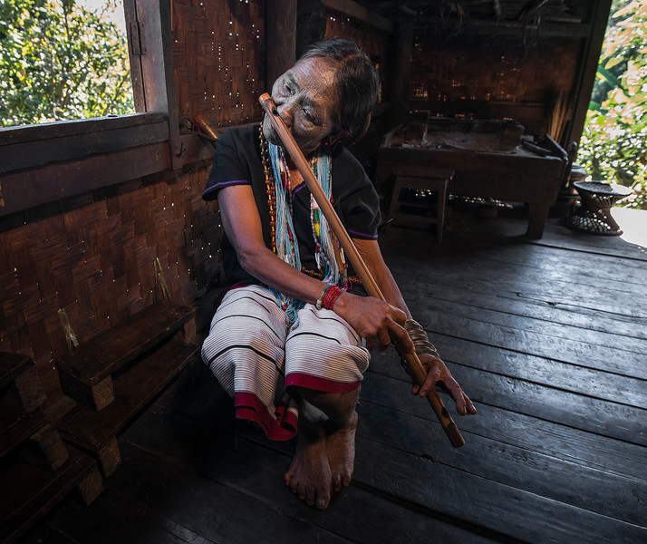 This is Pwe Htang a 70 year old lady from the Daai Tribe. She lives in a small hamlet outside Kampetlet. Pwe learned to play the nose flute and a small, harp type instrument at the age of 14.  She learned to play by watching others in the village. At the young age of 15 she decided to have her face tattooed. She recalls how there was a lot of pressure put on her by others in the village. They explained that she would not be able to find a husband without the tattoos. She did marry eventually but her husband died recently and she now lives with her only son.   Chin State, Myanmar, 2017