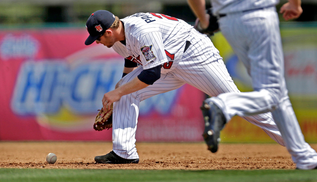 . Twins first baseman Chris Parmelee drops a ground ball but recovers to throw out Pittsburgh\'s Robert Andino on a ground-out in the first inning. (AP Photo/Gerald Herbert)