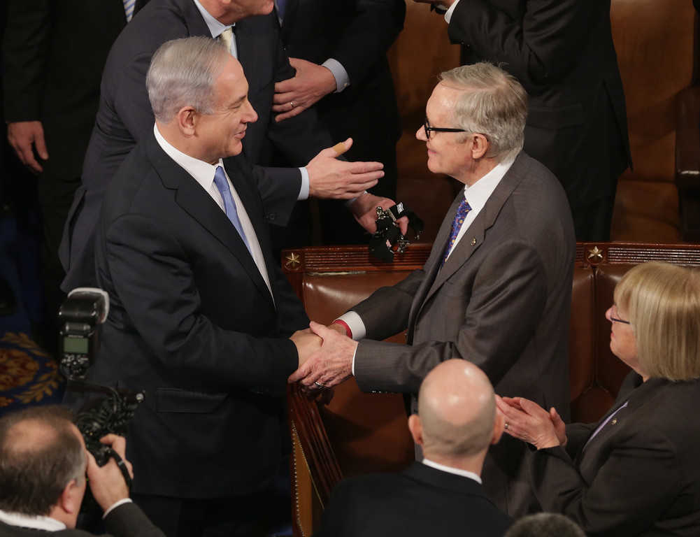 . Israeli Prime Minister Benjamin Netanyahu (L) is greeted by Senate Minority Leader Harry Reid (D-AZ) (R) before speaking to a joint meeting of the United States Congress in the House chamber at the U.S. Capitol March 3, 2015 in Washington, DC. At the risk of further straining the relationship between Israel and the Obama Administration, Netanyahu warned members of Congress against what he considers an ill-advised nuclear deal with Iran.  (Photo by Chip Somodevilla/Getty Images)