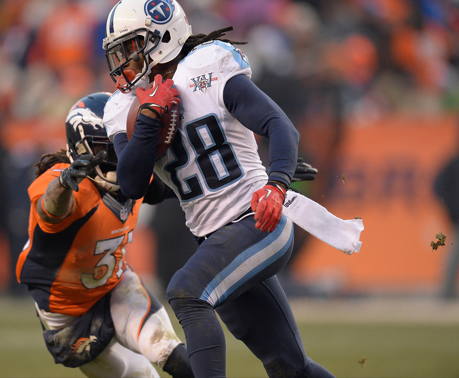 . Tennessee Titans running back Chris Johnson (28) tries to avoid a tackle by Denver Broncos cornerback Omar Bolden (31) in the third quarter.   (Photo by John Leyba/The Denver Post)