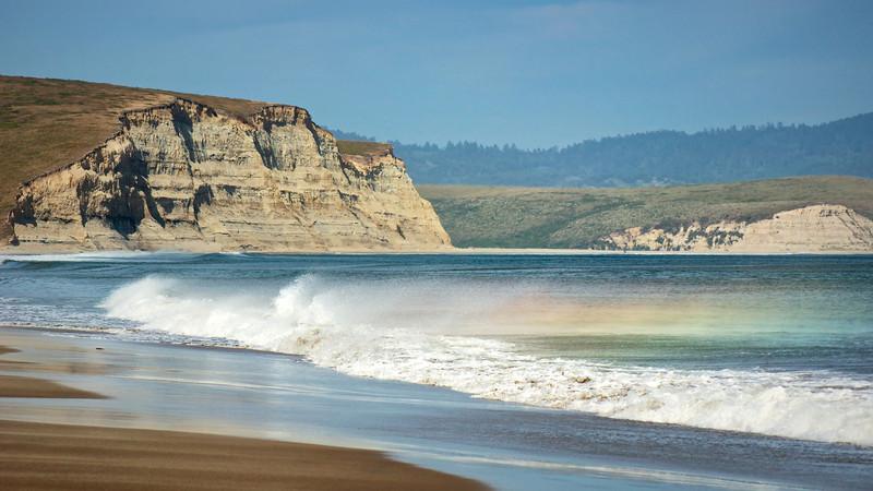 Rainbow in ocean waves. Drakes Beach, California Coast. ref: 518bd864-1db1-4b12-8f2b-539fa34d8c98