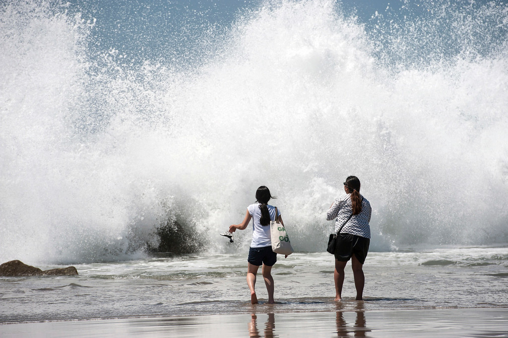 . Cece, left, and Jennifer, of Orange County, run as big waves crash the shoreline, Tuesday, Aug. 26, 2014, at Venice Beach, Calif. (AP Photo/The Orange County Register, Ed Crisostomo)