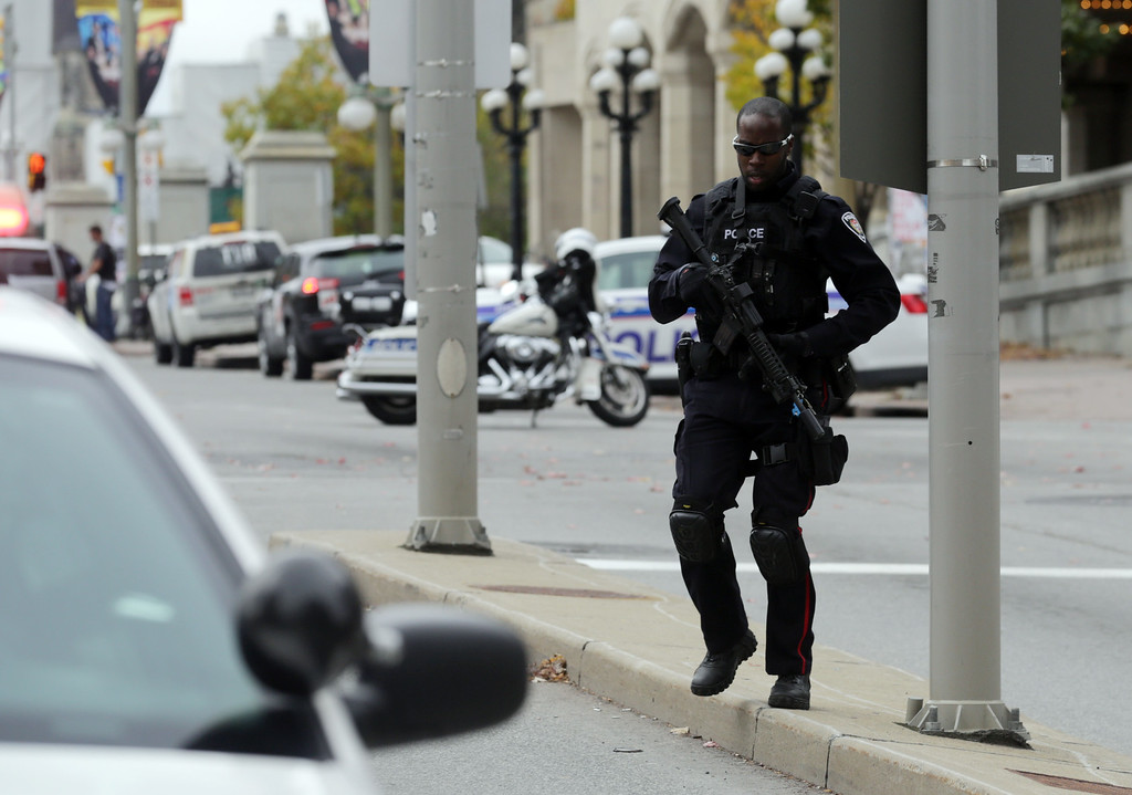 . An Ottawa police officer stands guard on Wellington St. near the National War Memorial where a soldier was shot earlier in the day, just blocks away from Parliament Hill, on October 22, 2014 in Ottawa, Canada. Officials are investigating multiple reports of shootings and suspects after at least one gunman shot a Canadian soldier and then entered Canada\'s Parliament building.   (Photo by Mike Carroccetto/Getty Images)
