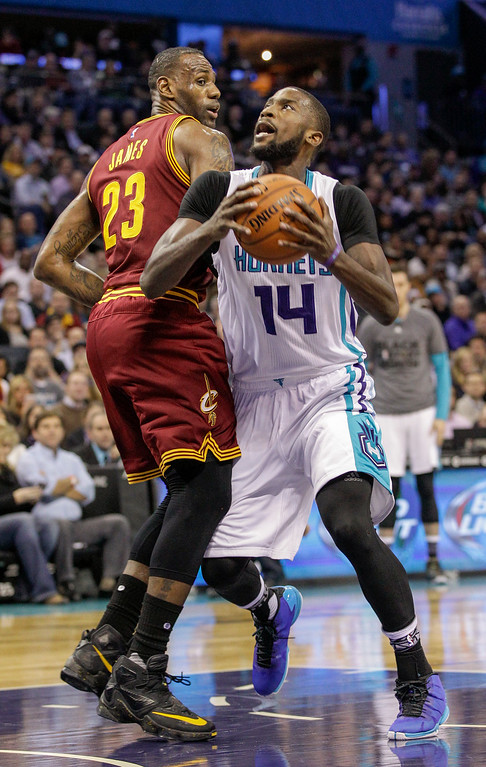 . Charlotte Hornets forward Michael Kidd-Gilchrist, right, drives into Cleveland Cavaliers forward LeBron James during the first half of an NBA basketball game Wednesday, Feb. 3, 2016, in Charlotte, N.C. (AP Photo/Nell Redmond)