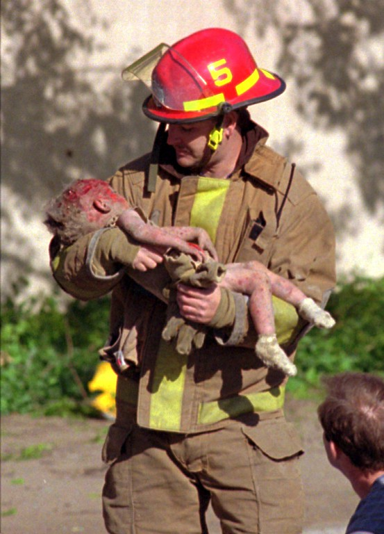 . Oklahoma City fire Capt. Chris Fields carries 1-year-old Baylee Almon, in this file photo shot Wednesday, April, 19, 1995 at the Alfred Murrah Federal Building in downtown Oklahoma City.  The child died of her injuries. (AP Photo/Charles H. Porter IV, File)