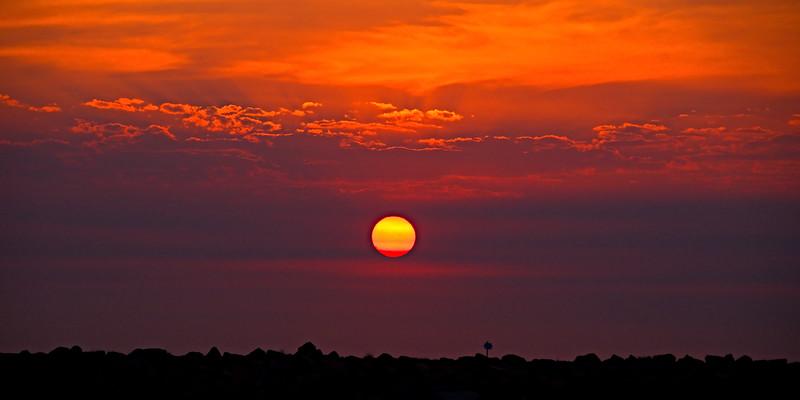 Golden Orange coastal sunrise cloudscape.