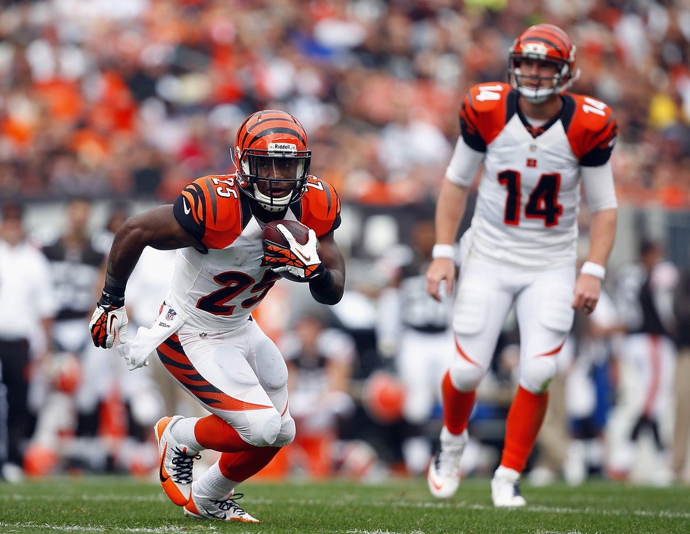 . CLEVELAND, OH - SEPTEMBER 29:  Half back Giovani Bernard #25 of the Cincinnati Bengals runs the ball as quarterback Andy Dalton #14 looks on against the Cleveland Browns at FirstEnergy Stadium on September 29, 2013 in Cleveland, Ohio.  (Photo by Matt Sullivan/Getty Images)