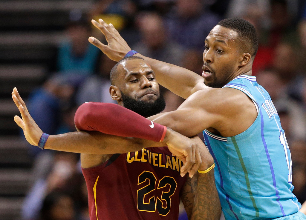 . Cleveland Cavaliers\' LeBron James (23) tries to break free of Charlotte Hornets\' Dwight Howard (12) during the first half of an NBA basketball game in Charlotte, N.C., Wednesday, Nov. 15, 2017. (AP Photo/Chuck Burton)