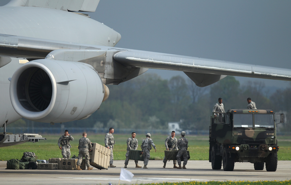 . Members of the U.S. Army 173rd Airborne Brigade unload equipment upon their arrival by plane at a Polish air force base on April 23, 2014 in Swidwin, Poland. Approximately 150 U.S. troops, as well as another 450 destined for the three Baltic states in coming days, will participate in bilateral military exercises over the coming weeks in a sign of commitment among NATO members. Tensions are rising in eastern Ukraine between Russian separatists and Ukrainian authorities and NATO is seeking to reassure its own members located close to Russia.  (Photo by Sean Gallup/Getty Images)