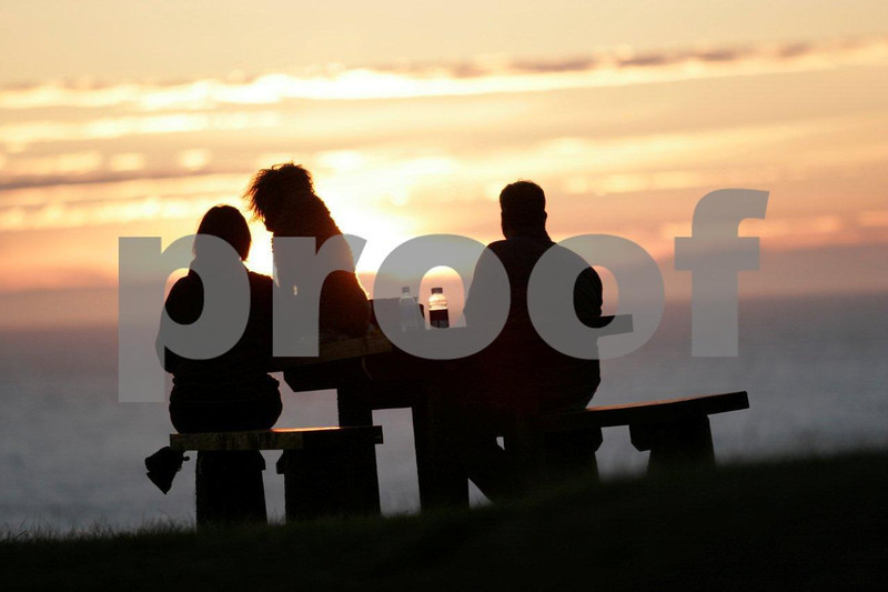 A couple at sunset sitting on a picnic table with their dog at Ecola State Park near Cannon Beach, Oregon.
