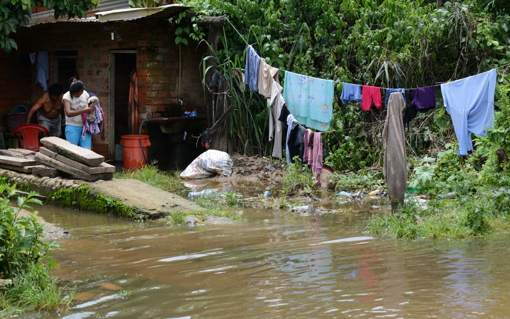 Description of . Locals attempt to recover belongings from their house flooded by the overflowing of the Beni river and heavy rains hitting the country, in Reyes, department of Beni, northeast Bolivia, on February 2, 2014. (AIZAR RALDES/AFP/Getty Images)