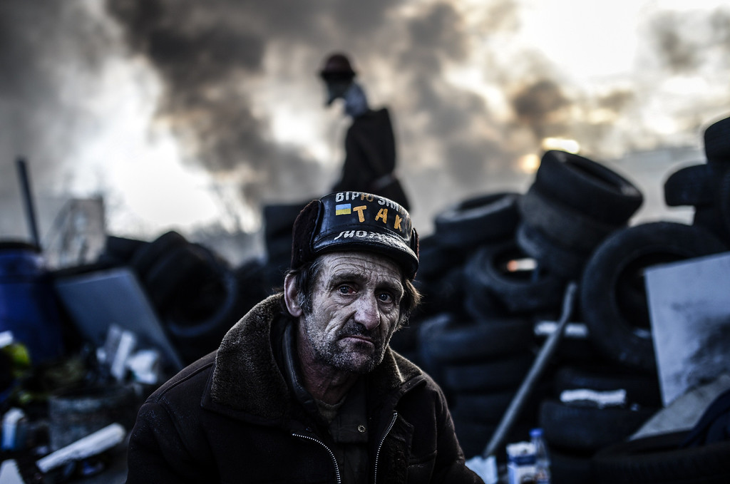 . An anti-government protester stays behind a barricade on February 21, 2014 in Kiev.  AFP PHOTO/BULENT KILIC/AFP/Getty Images