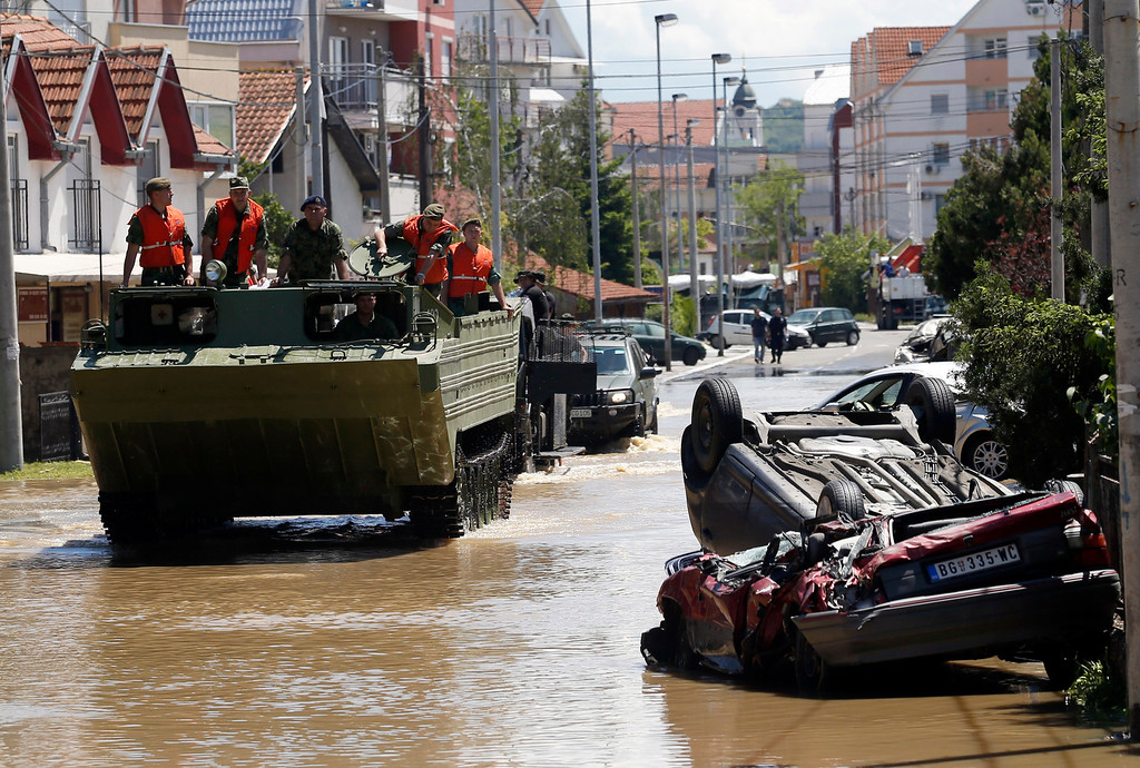 . A military amphibious vehicle drives through street where flood waters are retreating in Obrenovac, some 30 kilometers (18 miles) southwest of Belgrade, Serbia, Monday, May 19, 2014. Belgrade braced for a river surge Monday that threatened to inundate Serbia\'s main power plant and cause major power cuts in the crisis-stricken country as the Balkans struggle with the consequences of the worst flooding in southeastern Europe in more than a century. At least 35 people have died in Serbia and Bosnia in the five days of flooding caused by unprecedented torrential rain, laying waste to entire towns and villages and sending tens of thousands of people out of their homes, authorities said. (AP Photo/Darko Vojinovic)