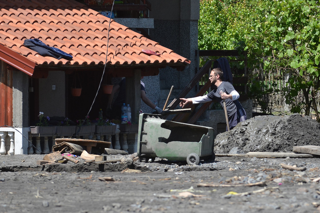 . Locals clear the earth from a home after a landslide in the flooded village of Topcic Polje, near the northern Bosnian city of Doboj, on May 19, 2014, after the river Bosna flooded entire agricultural fields and several urban areas along its flow during the weekend\'s rainfall, which also caused landslides.  AFP PHOTO / ELVIS BARUKCIC/AFP/Getty Images