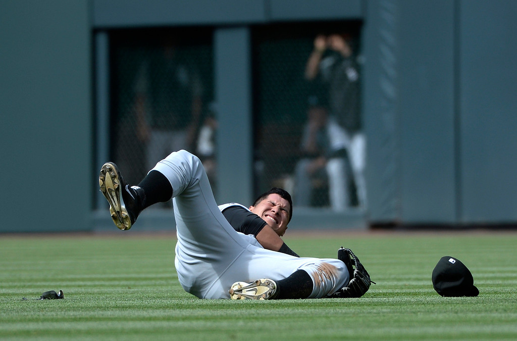 . Chicago White Sox outfielder, Avisail Garcia winces in pain after injuring his shoulder trying to catch a hit by Colorado Rockies second baseman, DJ LeMahieu in the sixth inning at Coors Field Wednesday afternoon, April 09, 2014. Garcia had to come out of the game. (Photo By Andy Cross / The Denver Post)