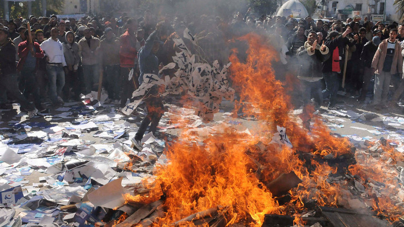 . Demonstrators burn documents of the Ennahda party, outside the party\'s headquarters, during a demonstration in Gafsa February 6, 2013. Thousands of Tunisians demonstrated outside the Interior Ministry headquarters following the slaying of secular opposition leader Chokri Belaid. REUTERS/Stringer