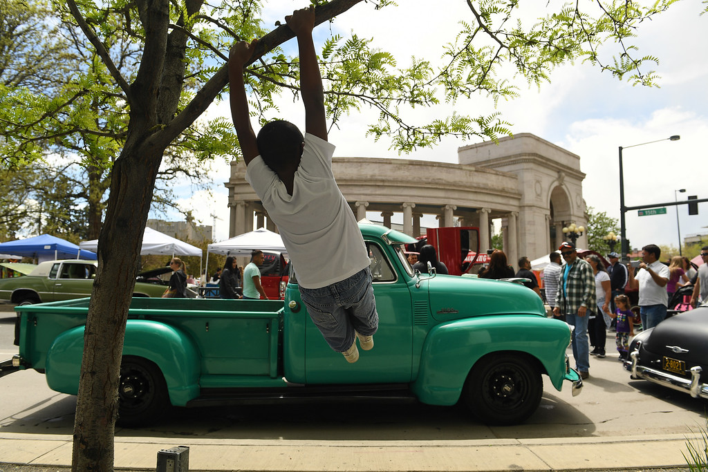. DENVER, CO - MAY 8:  Brandon Castro, 10, swings on a tree in front of a 1954 Chevy truck on display during Cinco de Mayo celebrations at Civic Center Park on May 8, 2016 in Denver, Colorado. (Photo by Helen H. Richardson/The Denver Post)