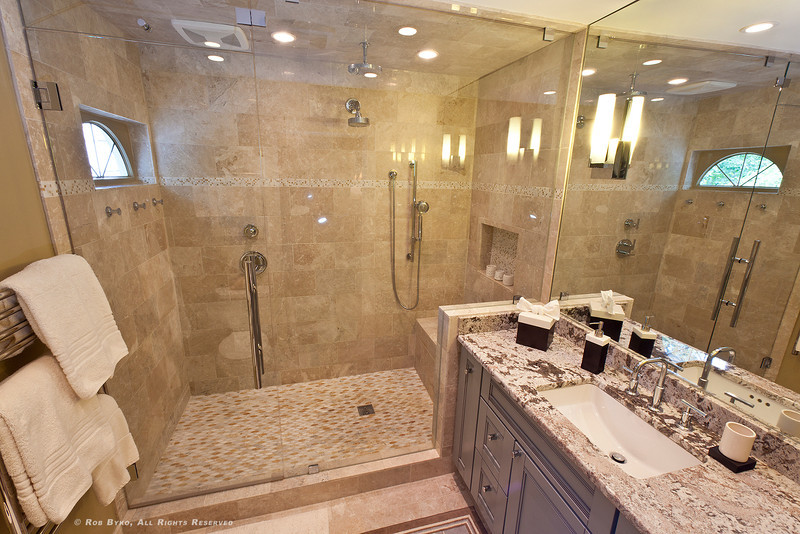 Get lost in the spacious, natural stone and glass-enclosed shower featuring two rain heads and hand-held wand, bench seat and recessed shelf, a heated towel bar and super-quiet exhaust fans both with programmable timer controls.