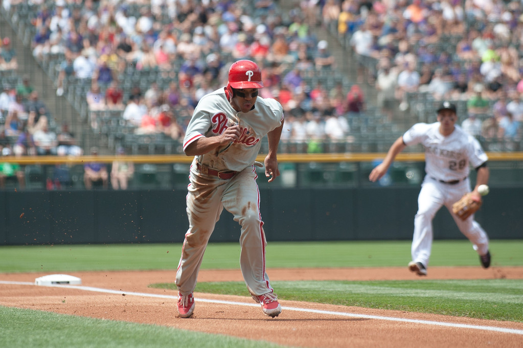. DENVER, CO - JUNE 15:  Ben Revere #2 of the Philadelphia Phillies scores from third base on an infield ground ball mishandled by Nolan Arenado #28 of the Colorado Rockies in the first inning of a game at Coors Field on June 15, 2013 in Denver, Colorado.  (Photo by Dustin Bradford/Getty Images)