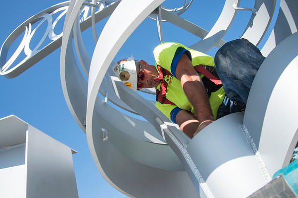 09/03/19 Wesley Bunnell | Staff The final bee statue was hoisted into place onto the Bee Hive Bridge by Sign Pro on Tuesday September 3, 2019. Spencer Brown stands inside the statue as he bolts the it into place.
