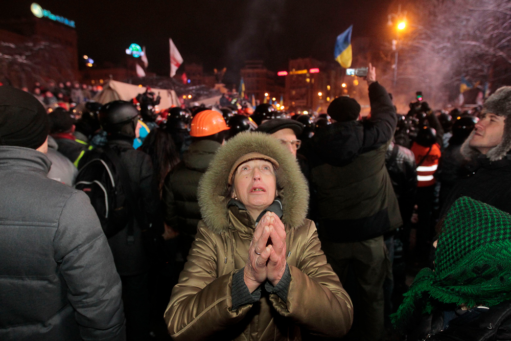 . A Pro-European Union activist prays as riot police going to storm an opposition tent camps on the Independence Square in Kiev, Ukraine, Wednesday, Dec. 11, 2013. Security forces clashed with protesters as they began tearing down opposition barricades and tents set up in the center of the Ukrainian capital early Wednesday, in an escalation of the weeks-long standoff threatening the leadership of President Viktor Yanukovych. (AP Photo/Sergei Chuzavkov)