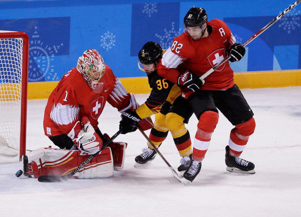 . Yannic Seidenberg, of Germany, center, shoots the puck past goaltender Jonas Hiller, of Switzerland, as Simon Moser, right, watches during the overtime period of the qualification round of the men\'s hockey game at the 2018 Winter Olympics in Gangneung, South Korea, Tuesday, Feb. 20, 2018. Germany won 2-1. (AP Photo/Frank Franklin II)