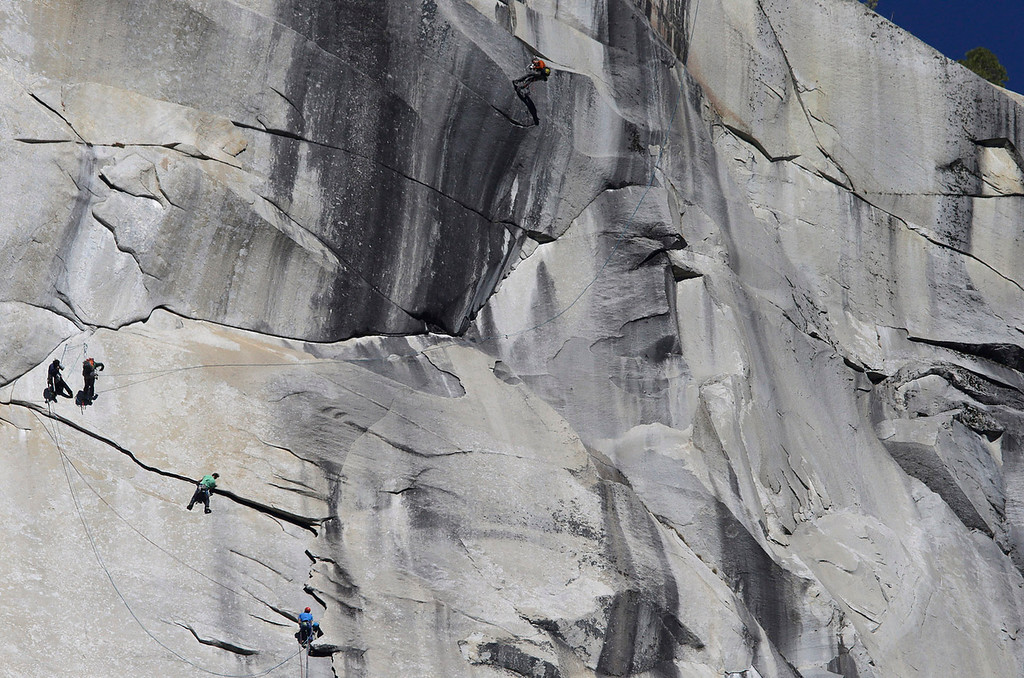 """. Kevin Jorgeson of California, wearing green, and 36-year-old Tommy Caldwell, wearing blue lower right, climb near the summit of El Capitan Wednesday, Jan. 14, 2015, as seen from the valley floor in Yosemite National Park, Calif. The two climbers vying to become the first in the world to use only their hands and feet to scale a sheer granite face in California\'s Yosemite National Park are almost to the top. Jorgeson and Caldwell have been attempting what many thought impossible. The men have been \""""free-climbing\"""" to the 3,000-foot summit for 17 days, meaning they don\'t use climbing aids other than ropes only to prevent deadly falls. Each trained for more than five years, and they have battled bloodied fingers and unseasonably warm weather. (AP Photo/Ben Margot)"""