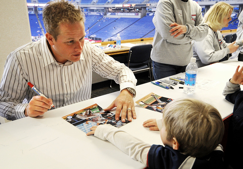 . Twins first baseman Justin Morneau talks with three year-old Sam Jacobson of South Haven, bottom left,  and his brother Graham, 5, bottom right,  during an autograph session in the football press box during the kick-off of the Twins Fest 2009 at the Metrodome on Friday night. (Pioneer Press: Sherri LaRose-Chiglo)