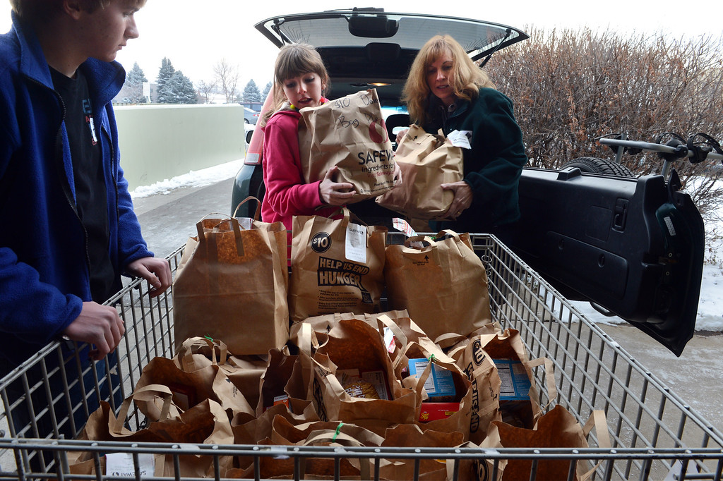 . Volunteers Trudie Demus and her children Justin, 14, and Madison, 11, deliver food donations to the Community Food Share in Longmont, CO, Thursday December 27, 2012.  Craig F. Walker, The Denver Post