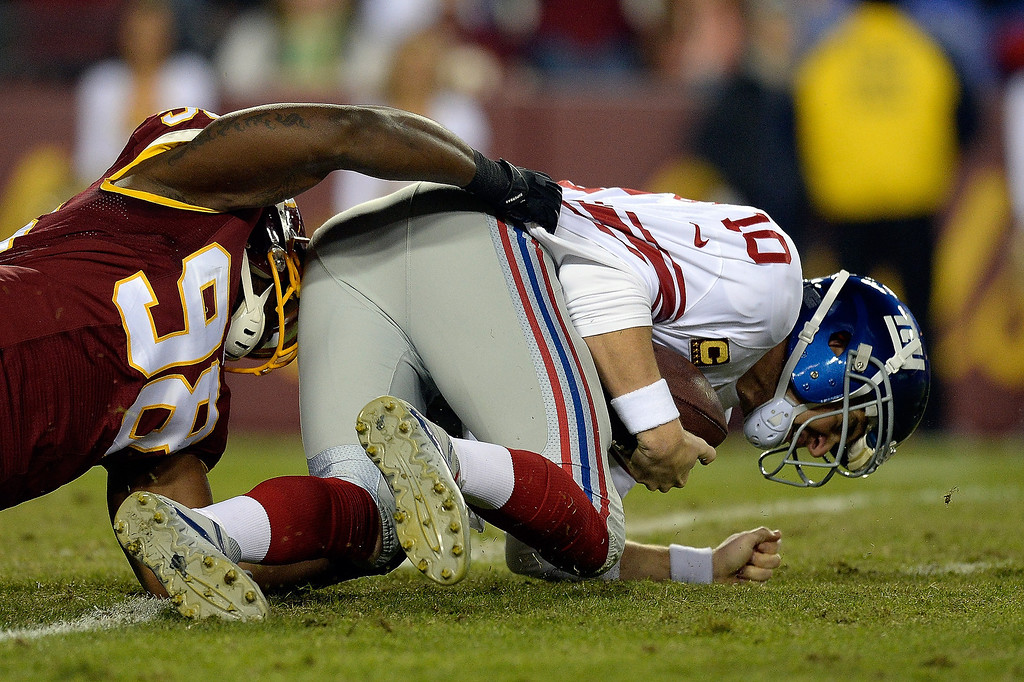 . LANDOVER, MD - DECEMBER 01:  Eli Manning #10 of the New York Giants is sacked by Brian Orakpo #98 of the Washington Redskins in the first quarter of an NFL game at FedExField on December 1, 2013 in Landover, Maryland.  (Photo by Patrick McDermott/Getty Images)
